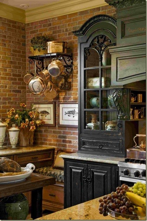 French Country Kitchen Black Cabinets Exposed Brick And Copper Pots Hanging From Black Scrolled Pot Rack