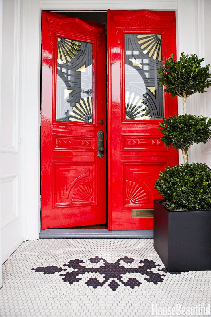 Red door with small tree on porch