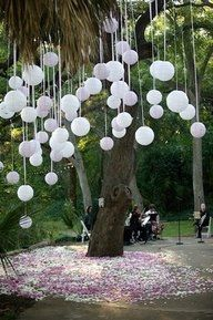 white hanging balloons - pop a marble in each balloon before blowing up cheaper than paper lanterns. you can also use glow sticks.....very pretty at night!! also battery operated tea lights