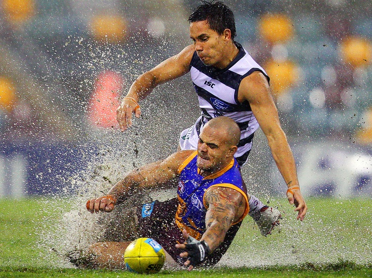 Wet and Wild - Ashley McGrath of the Brisbane Lions and Matthew Stokes of the Geelong Cats compete for the ball during their round five AFL match at the Gabba in Brisbane, Australia.
