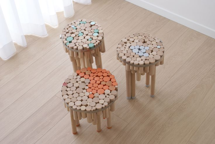 A series of tables in three sizes made from wooden dowels wrapped with a metal ring.    The design allows for a solid and stable structure without the need for glue or screws.