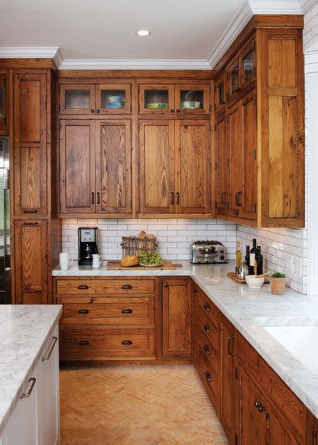 : Rustic Kitchen With Wooden Cabinets And White Tile Backsplash Above Brown Brick Floor Under White Ceiling