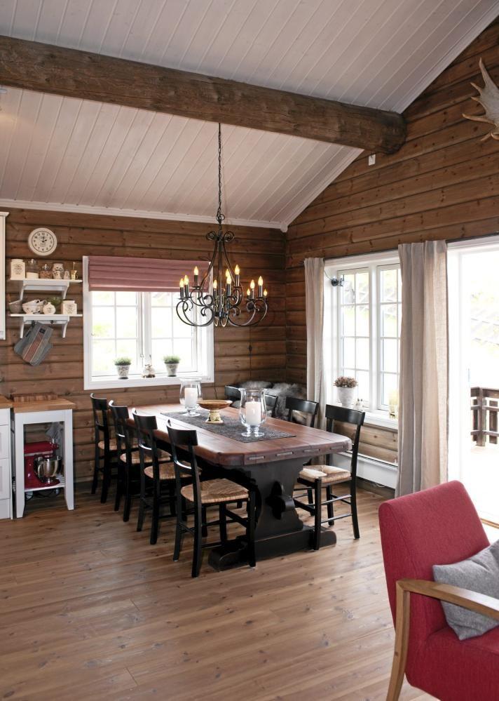 Hytta har en åpen løsning, med kjøkken, spisestue og stue i ett. Her er det satt opp rundtømmerpanel som gir en hyggelig atmosfære. Spisebordet er fra Dokka Bondemøbler og lysekronen er kjøpt hos Christiania Belysning.