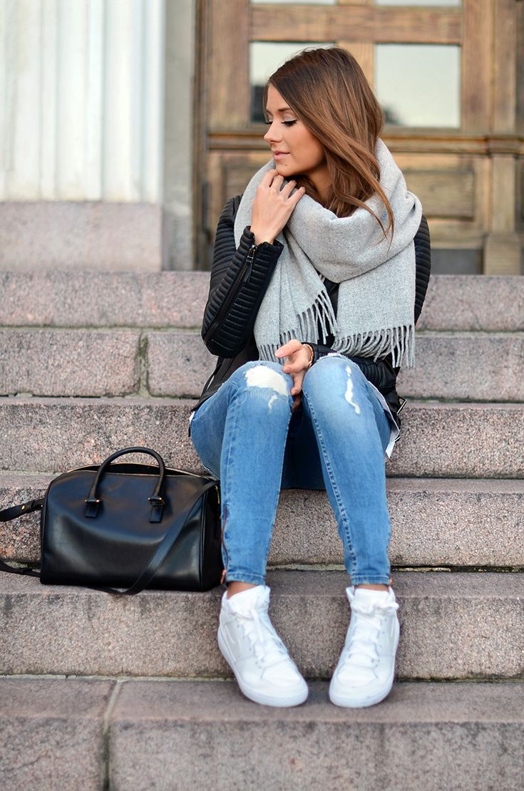 Chunky grey scarf and light jeans with a sleek black leather jacket