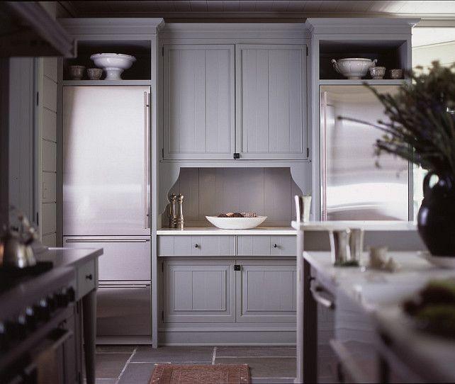Gray cabinetry, display shelving above refrigerators