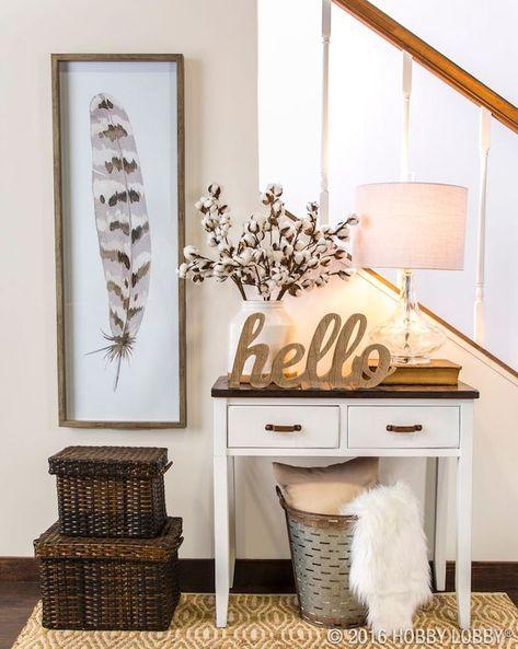 Treppenhaus in cremeweiß mit einem kleinen weißen Holztisch mit dunkelbrauner Tischplatte und zwei kleinen Schubladen mit braunen Griffen, Leselampe mit weißem Lampenschirm und Glasstand, gestellt auf einem dicken Buch, weiße Vase mit frischen Blumen, Hello-Dekoartikel aus Holz, Wäschekorb mit einem Kissen in Beige und einer weißen kuscheligen Plüschdecke, gestellt unter dem Holztisch, zwei Aufbewahrungskörbe aus Flechtholz in zwei Größen, schmaler Wandbild mit einem Vogelfeder mit drei…
