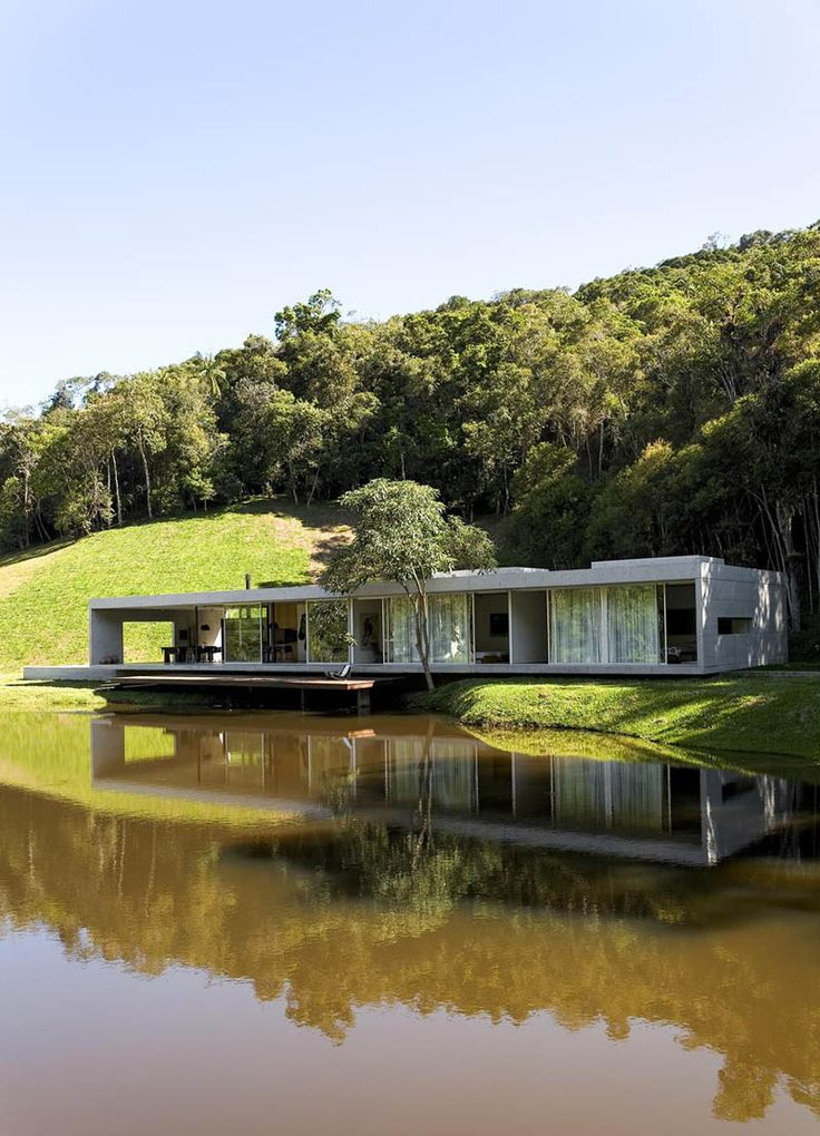 Découvrez un exemple pour construire une maison contemporaine avec une structure en béton située dans les bois au bord d'une rivière