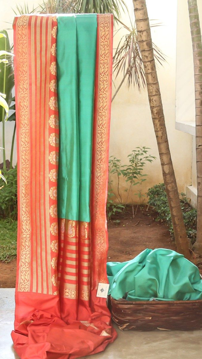 DAZZLING TURQUOISE BLUE HAS COMPLEMENTING SALMON PINK WITH GOLD ZARI FLORAL MOTIFS BORDER AND PALLU GIVING THE SAREE SMOOTH FINISH.
