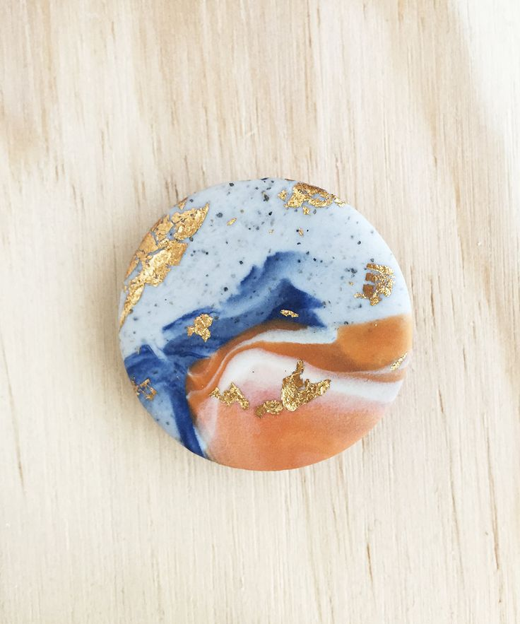 Circle brooch with a grey granite, orange and blue marbled colour palette by colourwork on Etsy