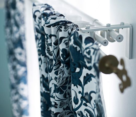 Close-up of a curtain solution consisting of three rods, brackets, finials and curtains