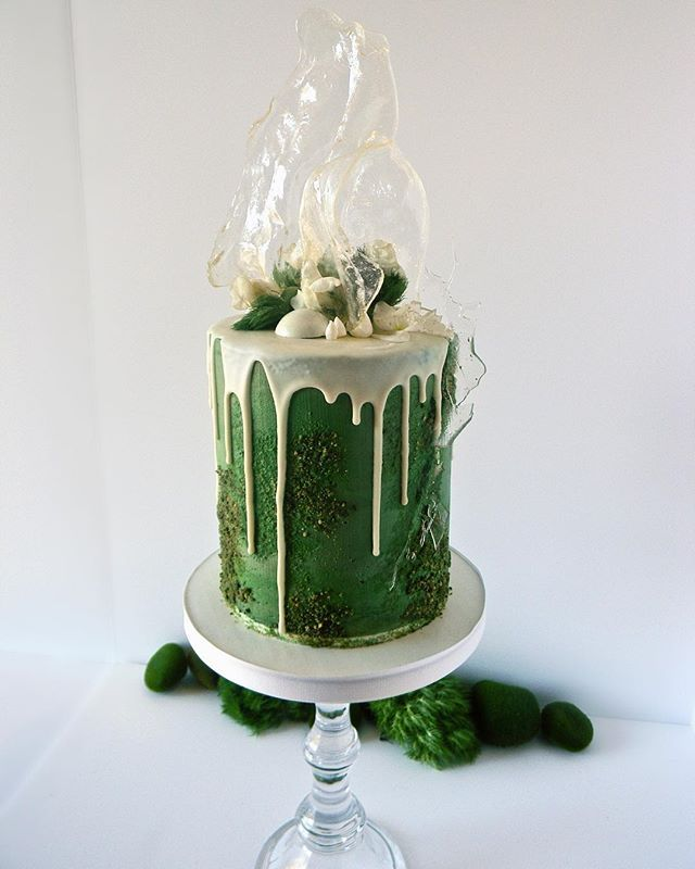 A mossy green drip cake with a tall sugar sail.
