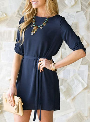 This is an adorable, casual mini dress that comes in a deep shade of navy blue. The dress has a high, rounded neckline and long sleeves. The sleeves are roomy enough to be comfortably pushed up above