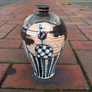 Metallic, red and blue glazed porcelain urn with Japanese influenced illustration