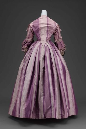 """A dress in two parts, of ombré purple taffeta, bodice boned and fitted coming to deep point center front and back, elbow length bell shaped sleeves with black and white lace and rose colored ribbon undersleeves, """"V"""" neck, hooked down center front, (b) skirt very full with fullness pleated to waistband all around, center front panel of skirt, edge of sleeve ruffles, front closing of bodice and yoke line of bodice trimmed with purple and gray silk chenille fringe; skirt lined throughout with…"""