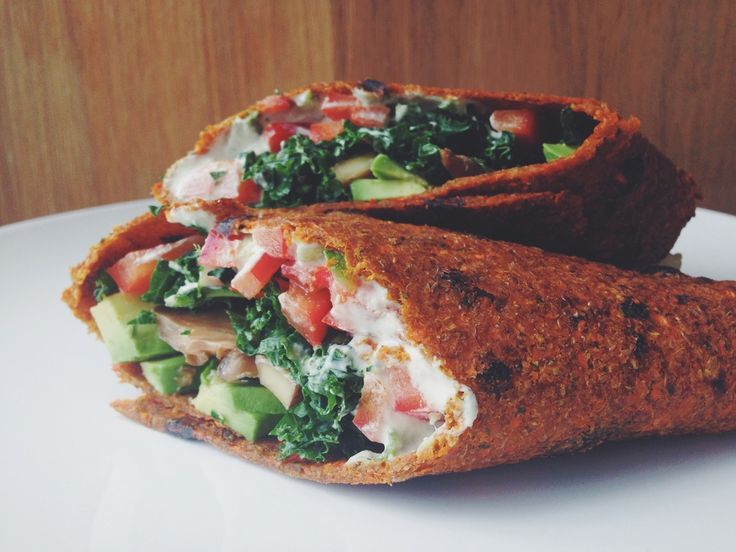Vegan sun-dried tomato carrot flax wraps stuffed with marinated mushrooms, avocado, red pepper, kale and cashew tzatziki