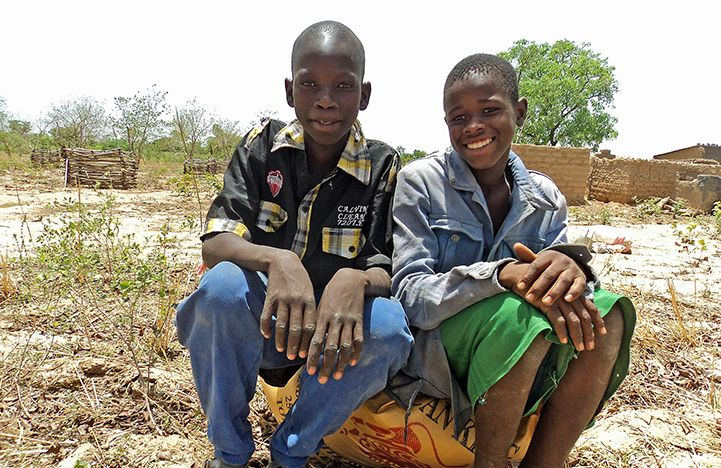 Two young Malians sitting on a bag of rice they have received. Bible Society is reaching out to displaced and impoverished families in Mali with Bibles and food aid.
