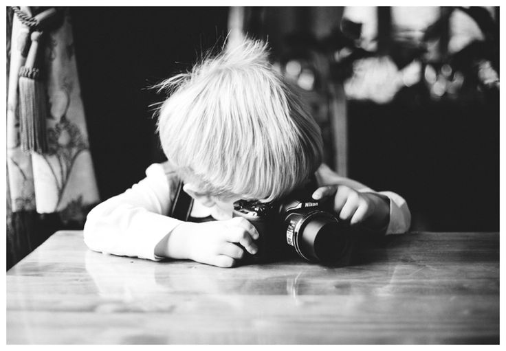 Young boy taking a photograph on a camera black and white www.ellen-richardson-weddings.com