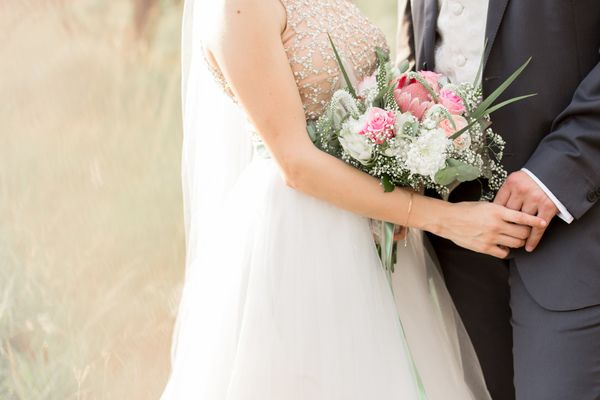 Rose gold and white wedding gown with pink and white rose flower bouquet