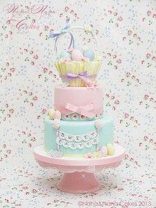 Di Nana & Nana (Cake Star)  Materiali: - base torta 22 cm - base torta 20 cm - base torta tronco di cono 12 cm - pasta di zucchero bianca, gialla, rosa,verde acqua, celeste, lilla - cmc - filo di ferro - sugar gun - cannuccia di carta colorata - colla edibile - scriber - pennello 00 - stampino ad espulsione blossom - cutter e venatore blossom medio - cutter e venatore petunia - perline di zucchero bianche e rosa - nastri raso rosa, celeste, giallo, verde acqua, lilla. Procedimento…