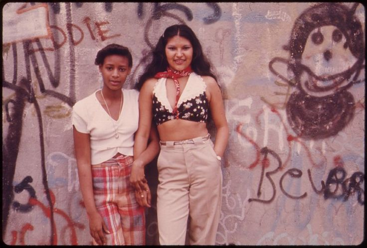 Two Latino girls pose in front of graffiti in Lynch Park, Brooklyn, June 1974.