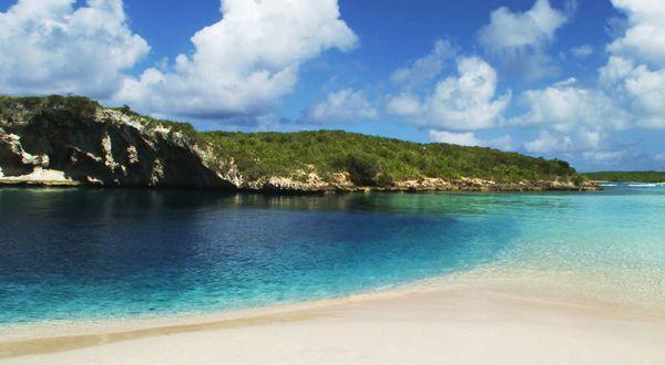 """MargaritaB/CreativeCommonsNão é o maior, mas trata-se do mais profundo """"Buraco Azul"""", com mais de 200 metros de profundidade. A tonalidade forte do azul é consequência da mistura de água doce, marinha e mistos que se estende abaixo do nível do mar. Acredita-se que há cavernas subterrâneas mais ao fundo nesse fenômeno abrigado na Long Island, Bahamas.."""
