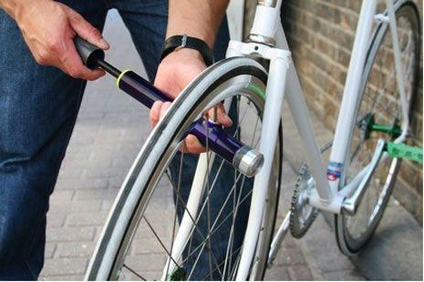 Inflador de ruedas de bicicletas  El trabajador está parado en una esquina con un inflador y la gente le lleva bicicletas para que las infle.