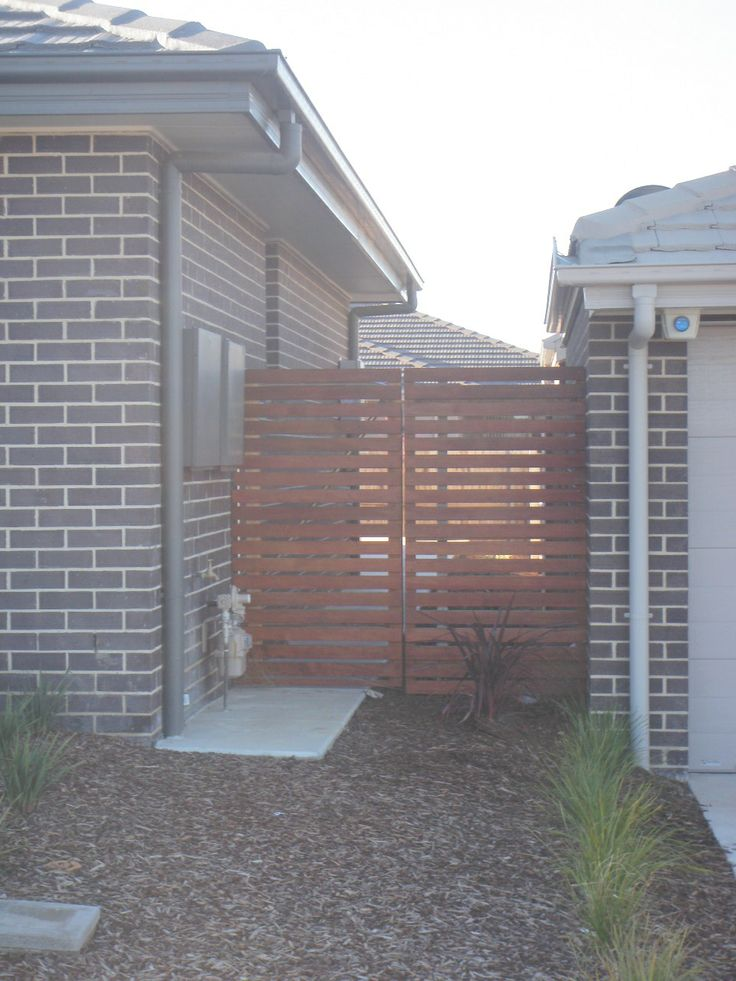 Courtyard wall will be built with brick pillars and wooden slats.  Fences must be like this according to Springbank Rise.
