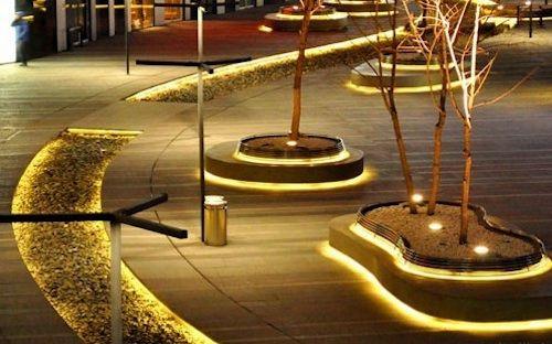 delle strisce led a luce calda usate per illuminare delle aiuole in un viale