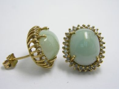 One pair of 18 karat yellow gold stud earrings. Two cabochon jadeite jade (12.75 carats, natural light greenish green). Fifty-six round brilliant cut diamonds (0.85 carats: SI1-I2 clarity: F-G colour).