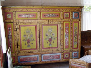 Wonderful old Swedish cabinet painted bright yellow with traditional kurbits designs. The room also has a painted bench and pine cradle.