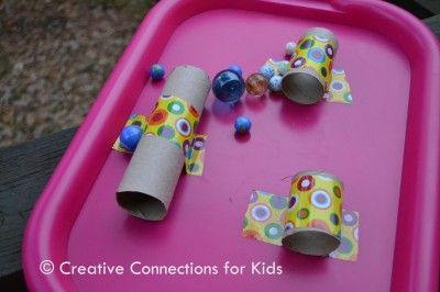 cut up a paper towel tube and tape the pieces to the tray and try to get the marbles to go through the tubes