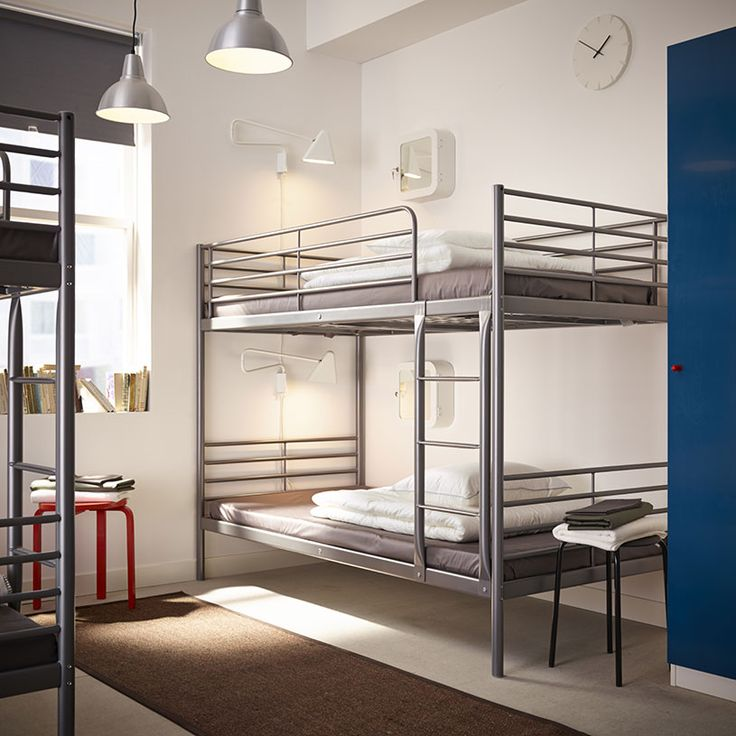A hostel with bunk beds in silver-colored steel