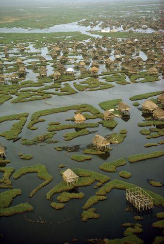 Many stilt houses of Dahomey village are scattered across a lagoon. {Ganvie, Benin, West Africa}