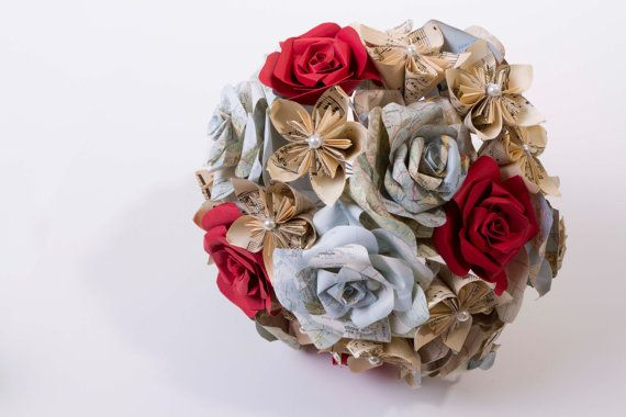 Beautiful wedding bouquet featuring vintage map roses, Antique (1912) music paper kusudama flowers with white glass pearl centre and accented with red paper roses.  Each petal is meticulously cutout by hand, carefully folded and individually glued together to create each flower.  This bridal set includes:  x1 Bridal bouquet  x1 groom boutonnière Would you like a different colour accent rose? Not a problem, just send me a conversation letting me know which colour you would like. Matching…