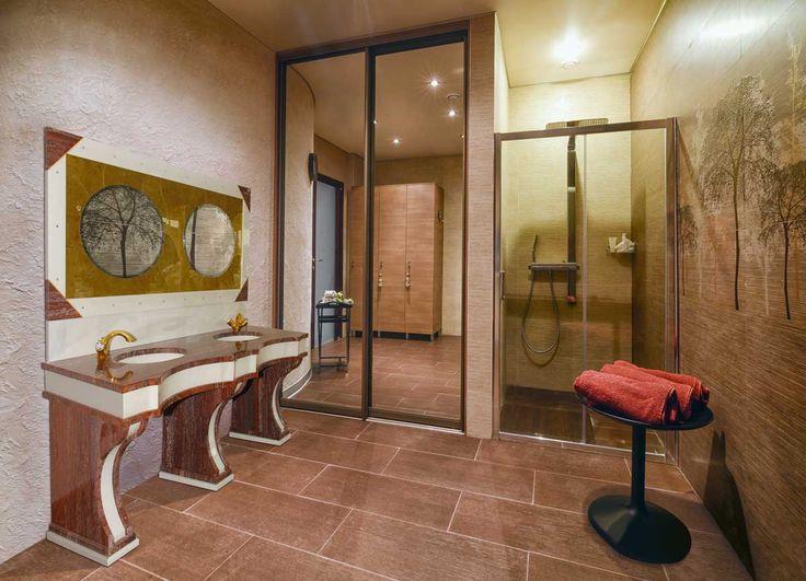 Bagno in materiale Santorini e bianco Lasa con rubinetteria lavata oro e cornice specchio con Swarovski e angoli foglia oro.
