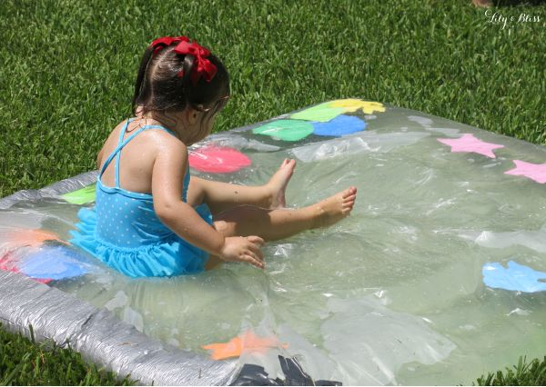 DIY water blob was such a HIT at our backyard birthday! Purchase plastic sheeting (from Lowe's) and seal the edges with duct tape...fill with water and poof...you have a fun squishy water blob! I inserted some foam shapes before I sealed the blob...next time I might put glitter and food coloring in the water!
