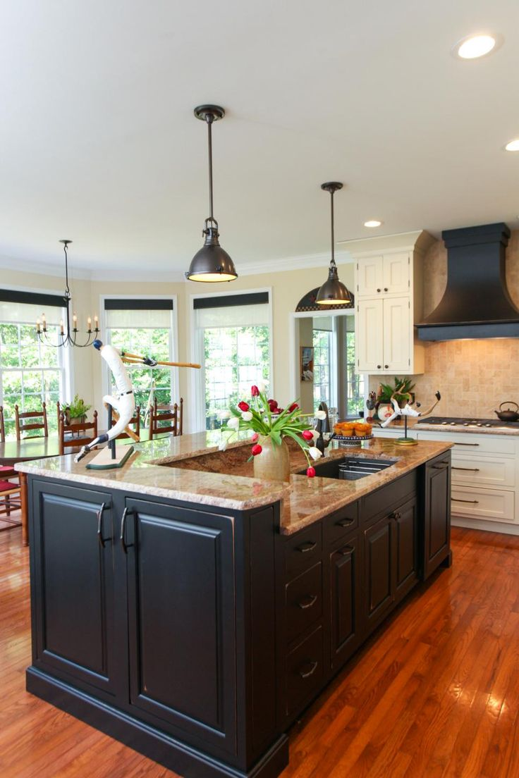 This large center island features black cabinetry and neutral granite countertops. Not only does it provide extra prep space, but with two counter heights, it has a bar top for eating or laying out a buffet. Black pendant lights add an industrial touch to the space.