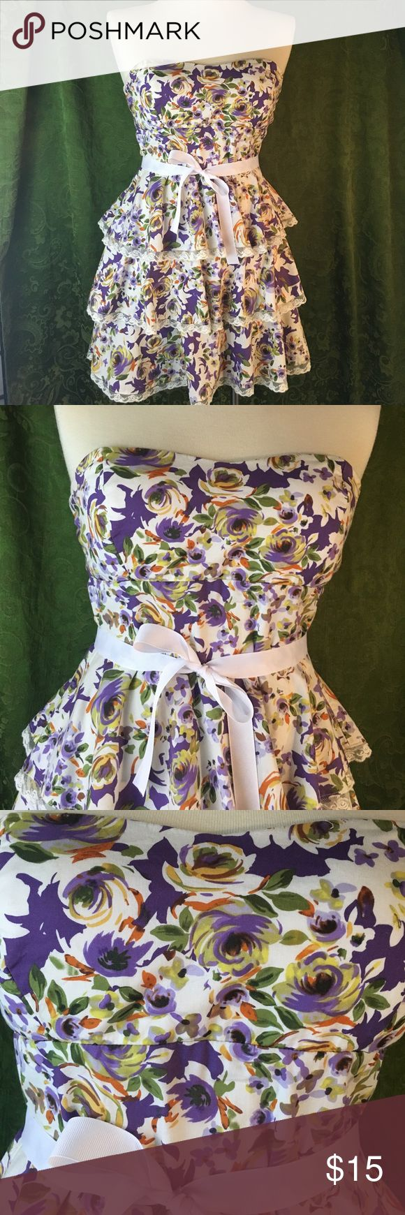 "B Smart strapless tiered floral sundress sz 10 Floral print in purple/green/yellow/orange on white with three tiers of ruffles, each trimmed in white lace. Cotton-rich (97%) with some spandex (3%) and a poly lining. Machine washable. Fully functional back zipper. Strapless with padded cups. Grosgrain ribbon belt. Perfect for a summer wedding or date. No holes or tears. EUC from a smoke free home. 16"" armpit to armpit. 15"" under bust. 14"" across waist. 18"" waist to hem. B Smart Dresses…"