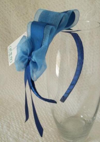 Diadema para celebraciones, forrada en raso y adornada con cinta de organdí y falla, rematada con una moña de organdí y raso.