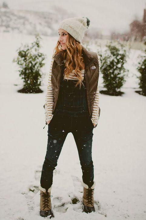 Snowy Days. White Beanie With Pom Pom, Olive Winter Vest, Dark Blue Overalls, Striped Long Sleeve Top, and Snow Boots!
