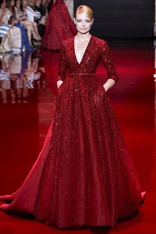 Ellie Saab ~ Sequins, shimmer, shine  crystals are very much the mainstay of this designer's creations.  Lush colors, textures.  This full-skirted gown flows out from a fitted bodice with 3/4 length sleeves  Deep V neckline.