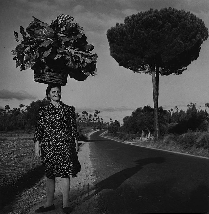 Charles Fenno Jacobs A woman carries her truck-garden produce on her head, Portugal, circa 1948-1955.