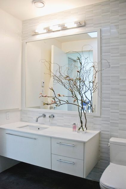 Shiny Porcelanosa tiles mix with matte white Ames Tile in the main bathroom. The curly willow and magnolia add to the spa-like feel of the modern space.   Vanity light: The Lighting Warehouse; vanity: custom design, Paula Guerra; vase: Pottery Barn; faucets: Huntington Brass; toilet: Duravit