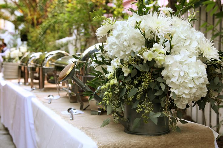 eclectic watering can centerpieces: white hydrangea, white spider mums, white freesia, white dendrobium orchids, white   mini calla lily, lemon leaves and seeded eucalyptus.