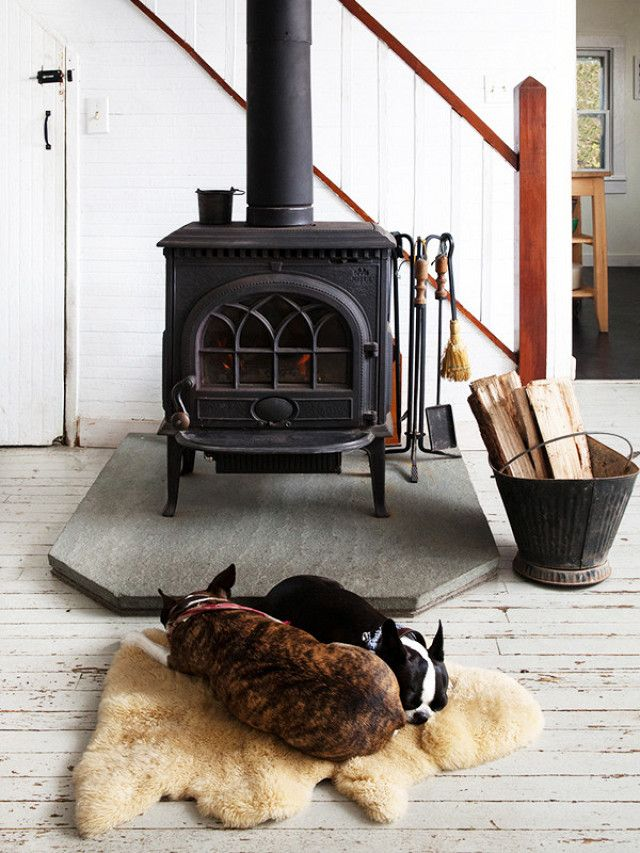 Fireplace set-up with a black-and-white palette, and layered natural tones like sheepskin and firewood