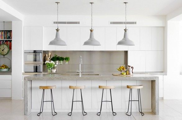 Concrete counters with matching pendants and barstools.