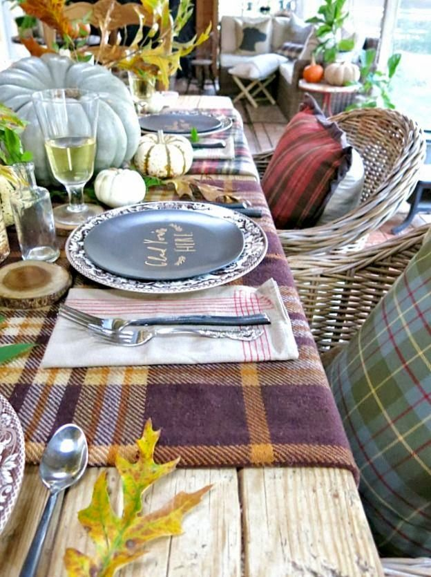 Gorgeous outdoor table setting for fall/autumn, featuring plaid blankets and other rustic accents.