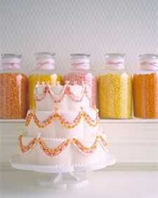 necklace-like garlands that appear to hang along the curves of three petal-shaped fondant-covered tiers