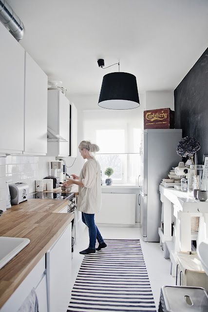 White walls, cabinets, and floors. Light wood countertops. Black decor. All combine to make a small kitchen open and contemporary. This particular look would be easy to create on a smaller budget.