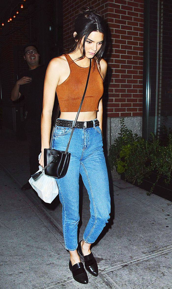 Kendall Jenner wears a crop top, high-waisted belted skinny jeans, a mini bucket bag, and loafers
